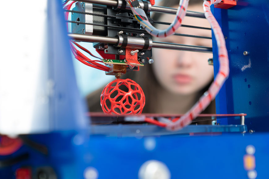 A young woman looks at a 3D printer creating a ball-shaped prototype