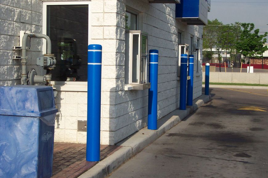 Blue bollards circled with white reflective tape protect a fast-food drive through