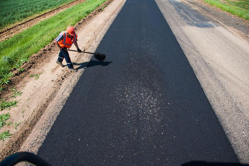 Construction worker uses shovel to move asphalt