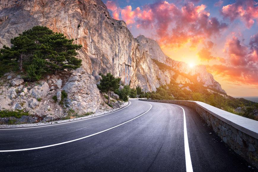 Winding asphalt road at sunset