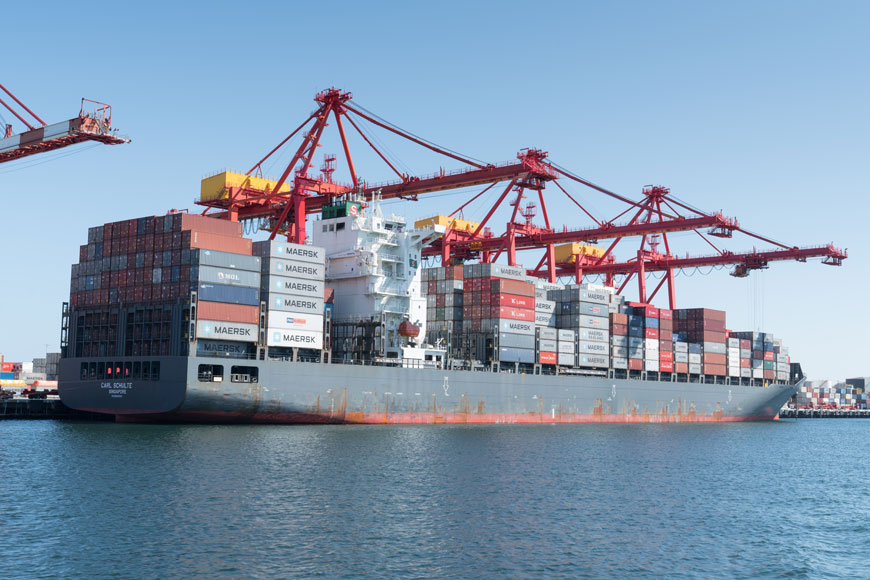 A cargo ship covered in shipping containers sits in port