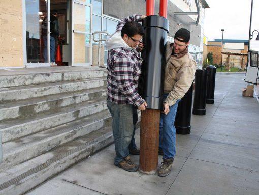 Two people installing R-1007-08 steel pipe security bollard