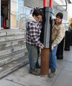 Two men installing R-1007-10 steel pipe security bollard
