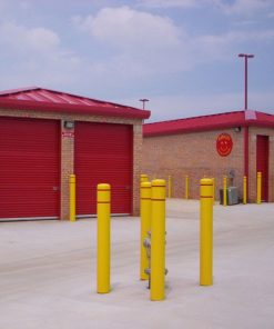 R-7110 plastic bollard covers outdoors in front of red buildings