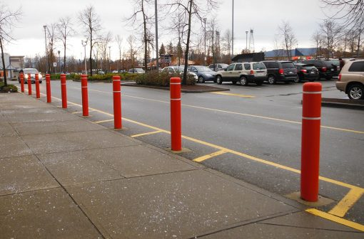 Line of red R-7109 plastic bollard covers on street