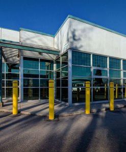 Yellow R-7110 plastic bollard covers protecting building perimeter