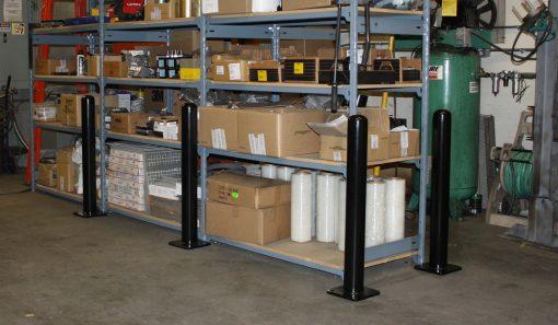 Black R-7236 bolt down bollards protecting shelves at warehouse