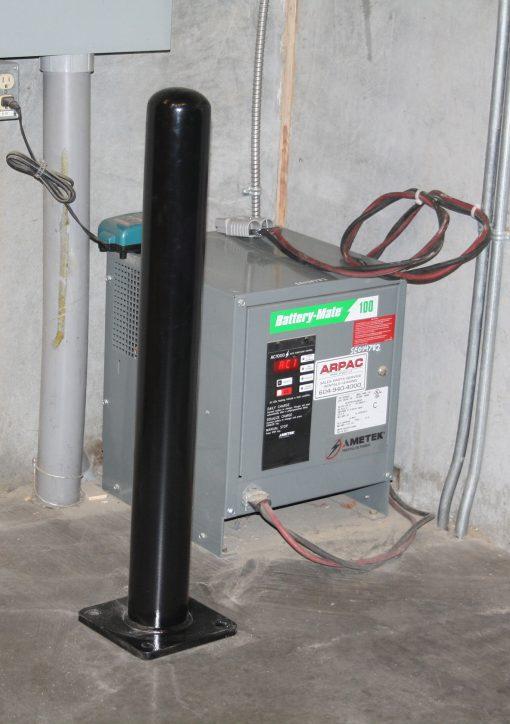 Black R-7236 bolt down bollard protecting utility box