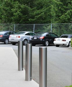 Three R-7303 stainless steel bollard covers with cars in the background