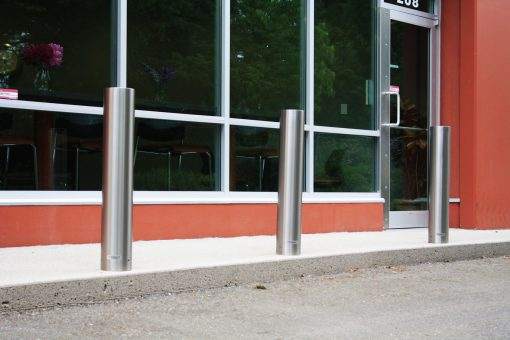 R-7303 stainless steel bollard covers along concrete curb