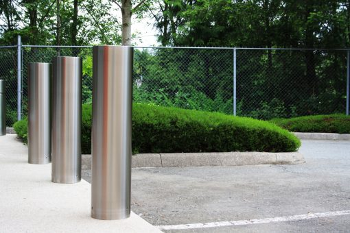Three R-7307-EX stainless steel bollard covers in parking lot