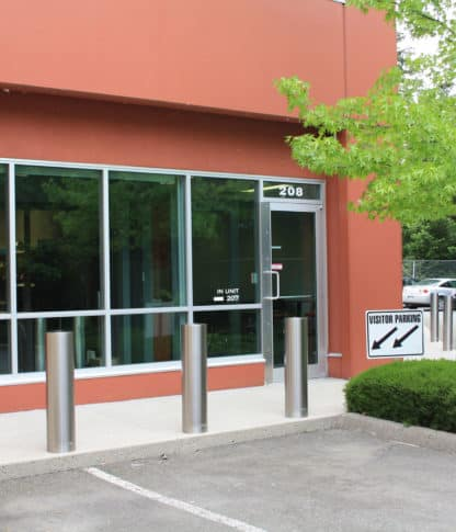 Three R-7311 stainless steel bollard covers at front of parking stalls