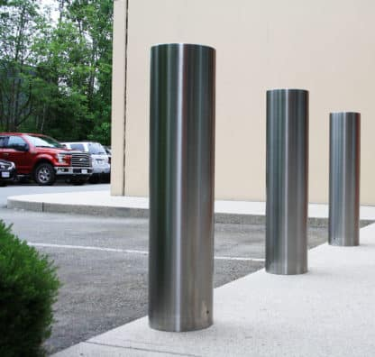Three R-7311 stainless steel bollard covers in parking lot