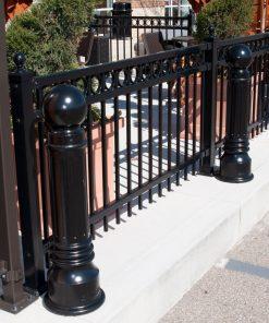 Three R-7539 decorative bollards along iron fence
