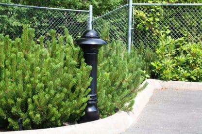 R-7552 decorative bollard by curb near green bushes