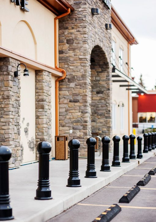Row of R-7592 decorative bollards in front of brick building