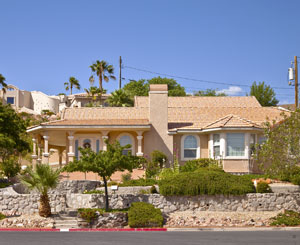 Large pink house with stucco and tiled roof sits behind Palm trees
