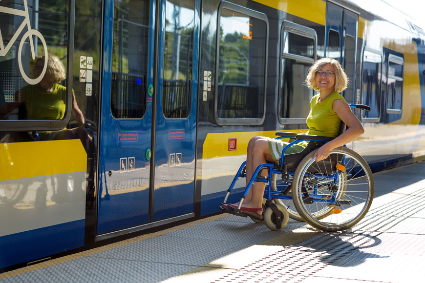 A woman in a wheelchair waits to board a bus on a platform with accessible design elements like buttons at two heights, bright contrasting clear information, and detectable warning plates