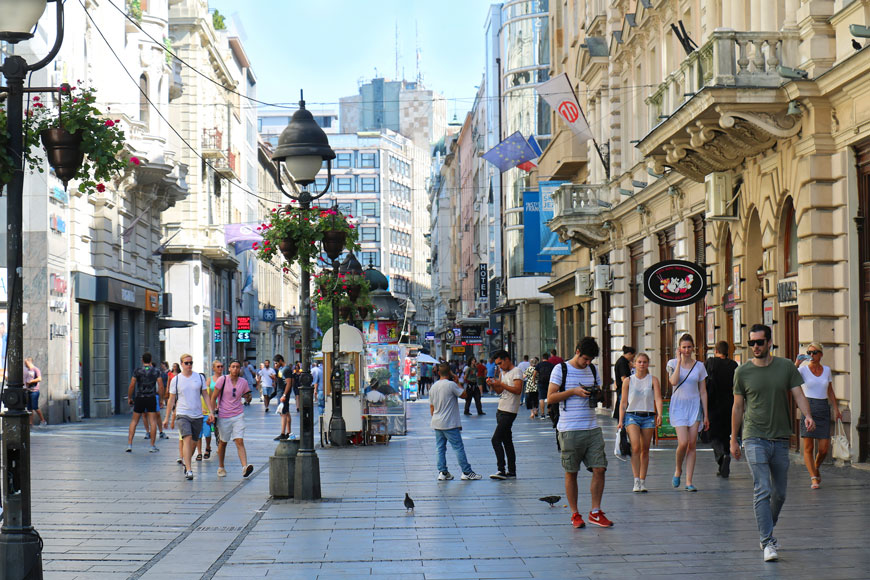 Many people walk through a bright shop-lined square in downtown Belgrade