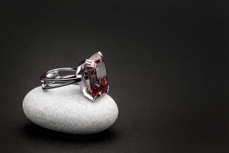 An emerald-cut ruby of substantial size in a white-gold setting sits on a white quartz rock on a dark background.
