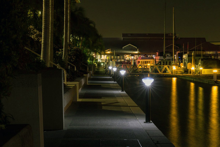 Architectural lit bollards dot the front of a marina and caution people away from the edge