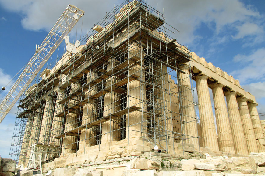 An image of the many Doric columns of the Parthenon surrounded by a nest of scaffolding for restoration work