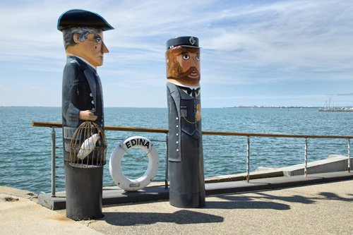 carved wooden bollards of sea captains stand on a wharf
