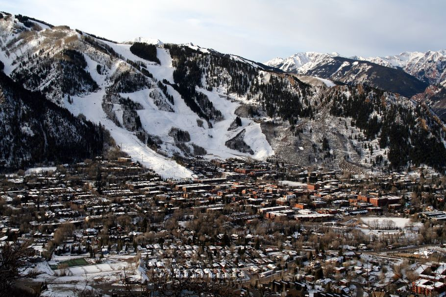 A picture from a drone of the city of Aspen in winter, rows of houses in front and the snow covered mountain rising behind