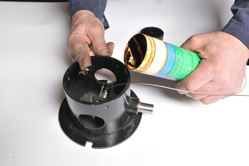 Assembly grease being applied to retractable bollard's internal mechanisms