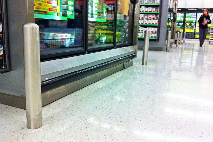 Stainless steel asset-protection bollards protect the corners of freezers in a grocery store.