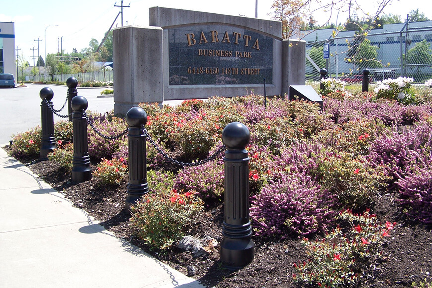 Bollards with chains protect a garden and office sign