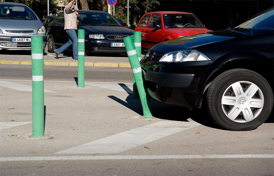 A black sedan colliding into a bumper post in a parking lot