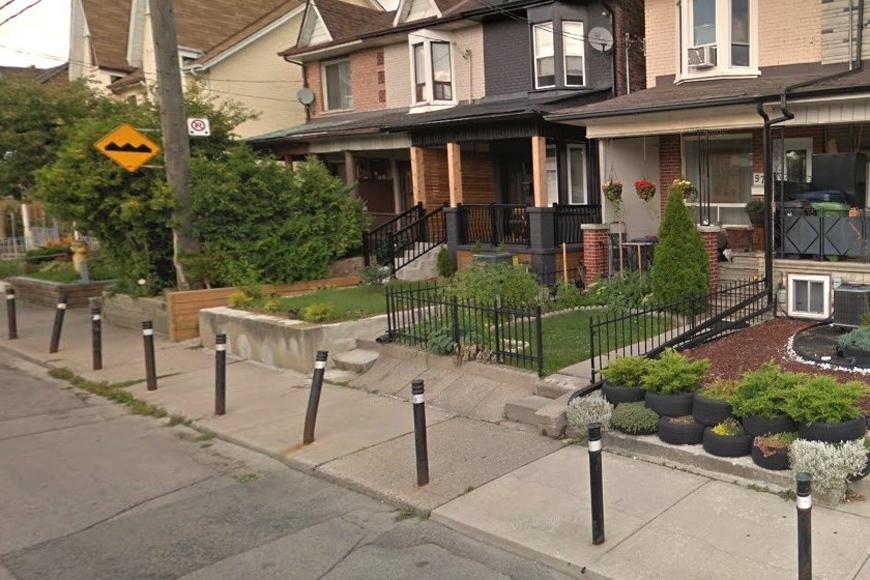 On a narrow urban sidewalk, mid-block bollards protect a line of homes
