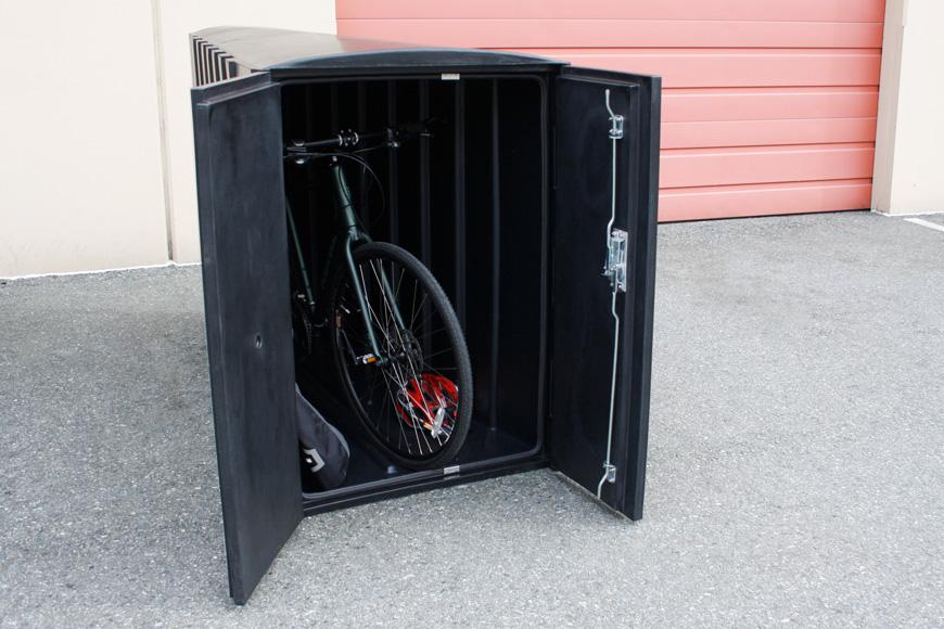 An open black bike locker contains a bike, a helmet, and a pannier.