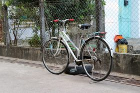 A bicycle stands by a car tire near a fence with a hazardous grate in front of it