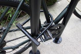 A black U-lock is filled by wheel, bike frame, and commercial bike rack