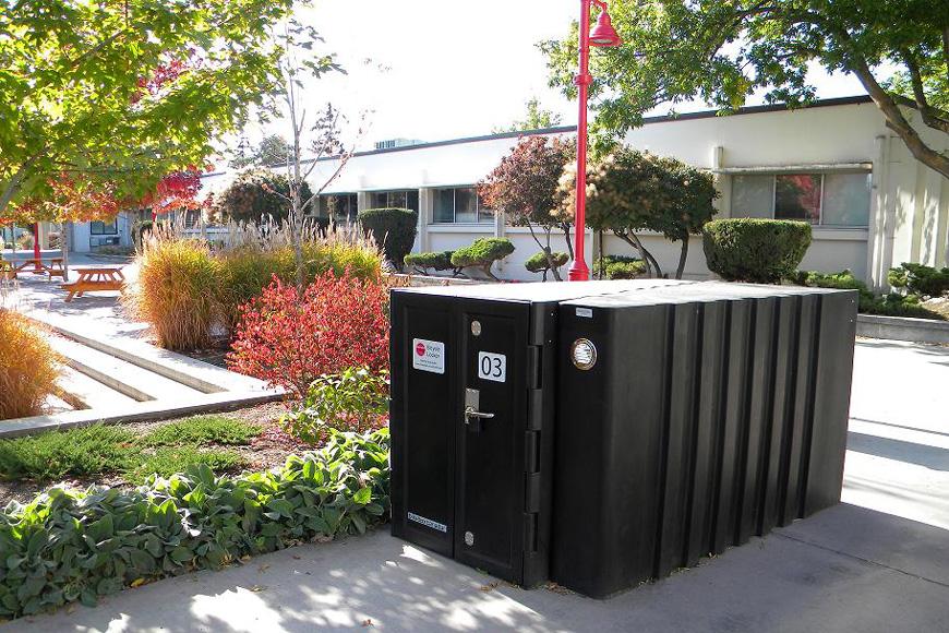 Des casiers à vélos en forme rectangulaire offrent un stationnement sécurisé devant un édifice