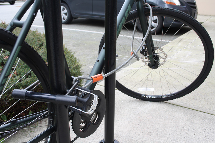 A dark green bike is locked with a u-lock in the back triangle, cabled to the front wheel