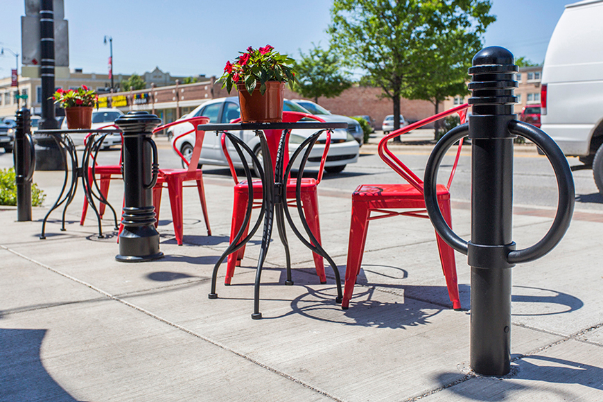 Decorative bicycle bollards enhance a patio with red chairs and tables in front of a café