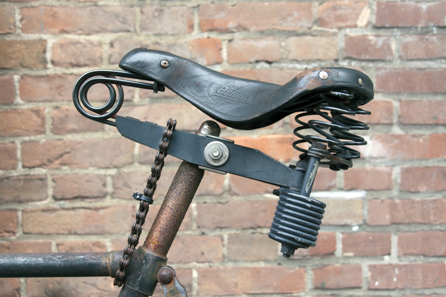 A custom bike seat on an older bike is locked on with bicycle chain
