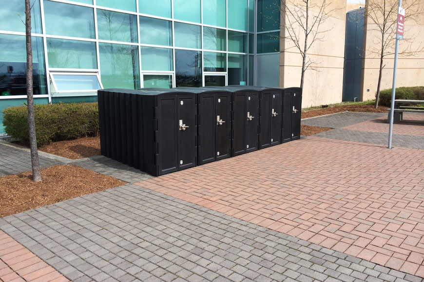 A row of bike storage lockers sit outside a building.