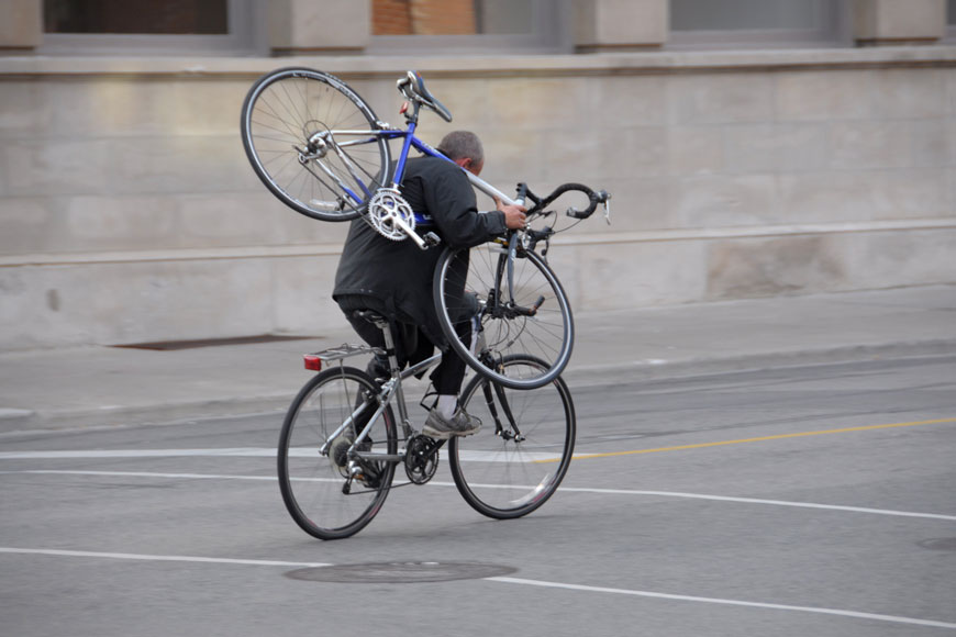 a bike thief rides away with a second bicycle