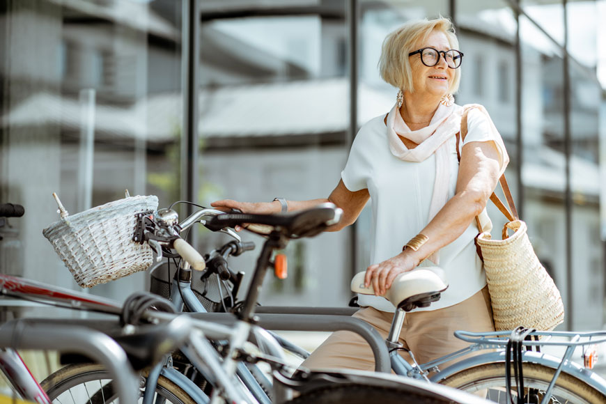 An older woman parks her bicycle while doing her regular errands