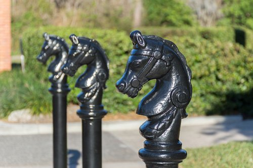 black artistic bollards with horse-head caps line a pathway