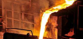 At a foundry, hot molten steel flows from a blast furnace before being cast into ingots