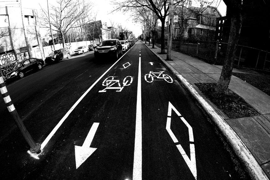 A black and white fish-eye photo shows a bidirectional separated bike lane