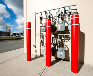 Three bright red bollards with reflective tape protect several utility meters outside a building
