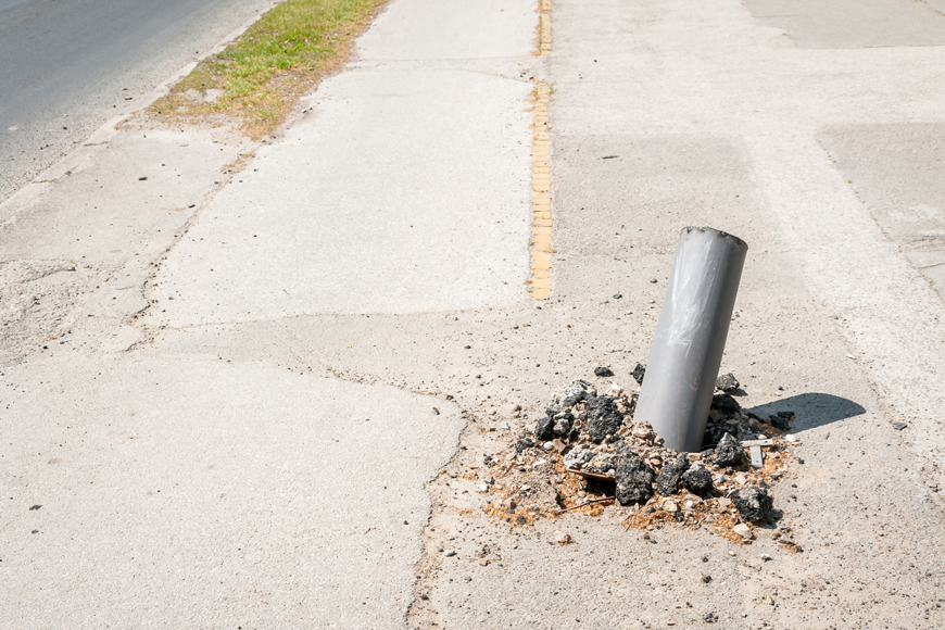 A bollard lies on an angle, having been pulled from the surrounding cement