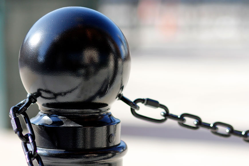 A bollard with hook and eye chains helps create a physical barrier
