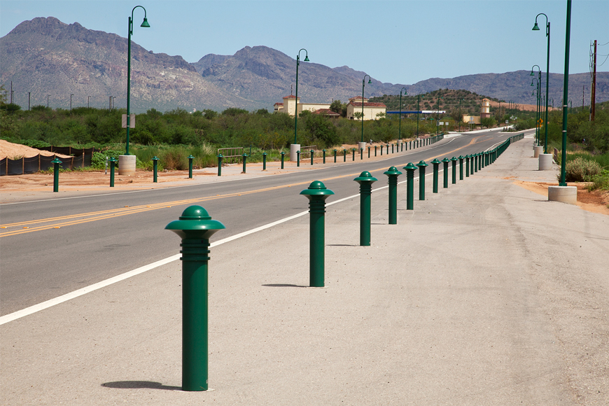 An empty road running toward rocky brown mountains is lined by scrubby bushes and green bollards.